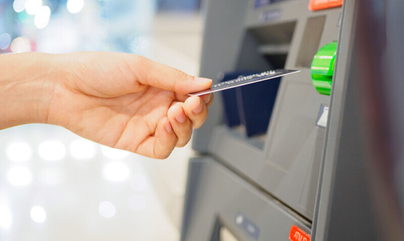 woman inserting debit card into atm