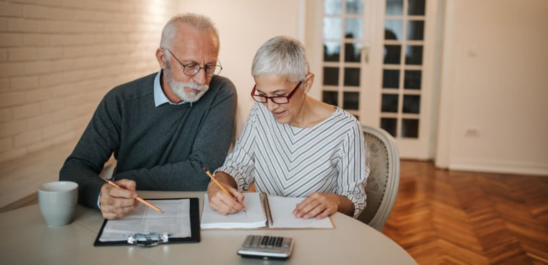 A senior couple taking a closer look at their budget in the comfort of their home