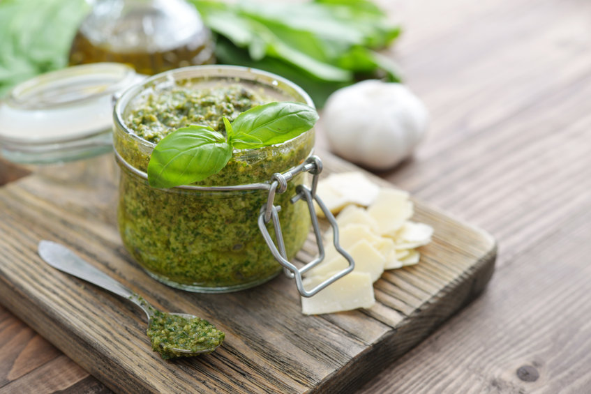 Fresh made Pesto Sauce in glass jar on wooden background